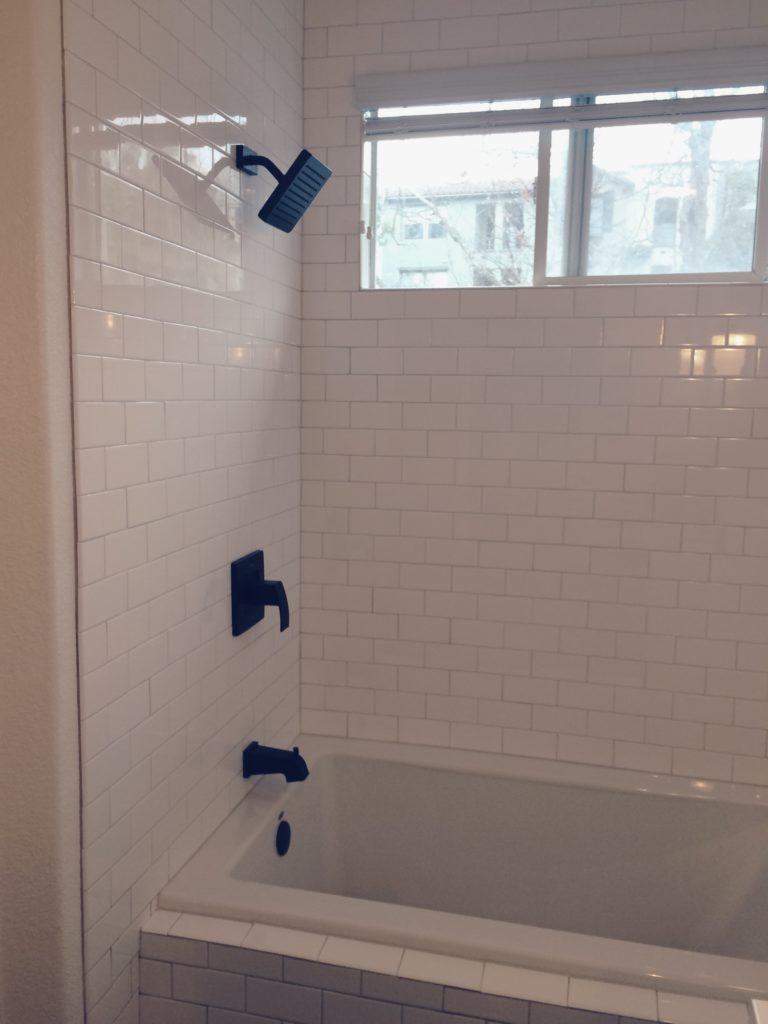 Matte Black Faucets and white subway tile bath