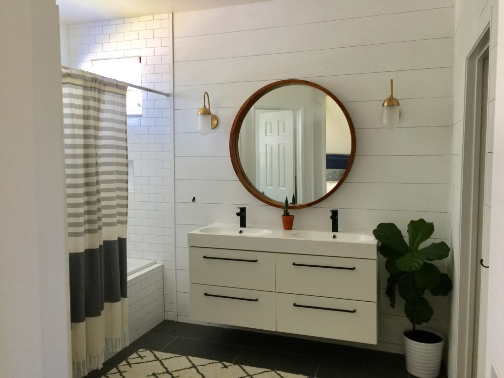 modern bathroom remodel with shiplap walls and brass sconces