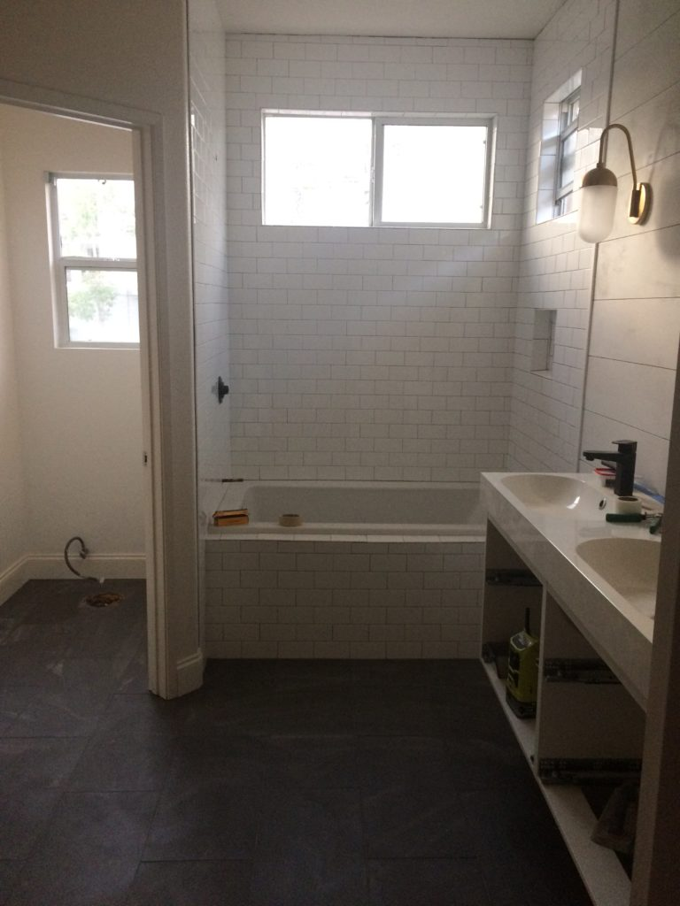 during construction of our bathroom remodel with dark gray tile